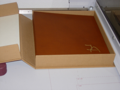 custom box housing wedding album, die with initials of couple gold stamped on to cover